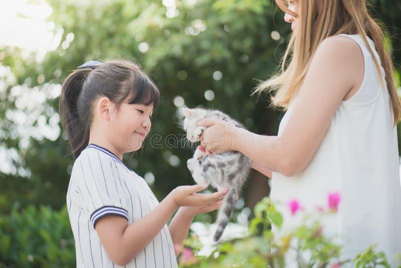 Mãe que dá um gatinho a sua filha fotos de stock royalty free