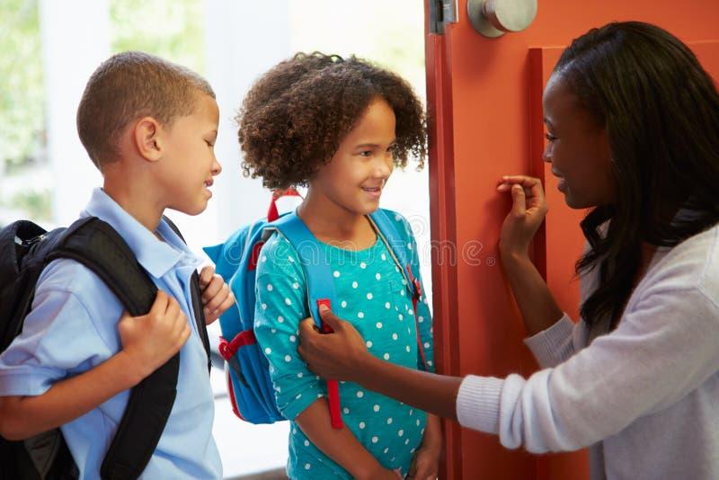Mãe que diz adeus às crianças como saem para a escola imagens de stock