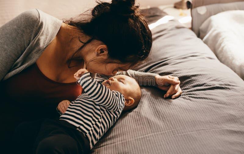 Mãe que encontra-se na cama com seu bebê fotografia de stock