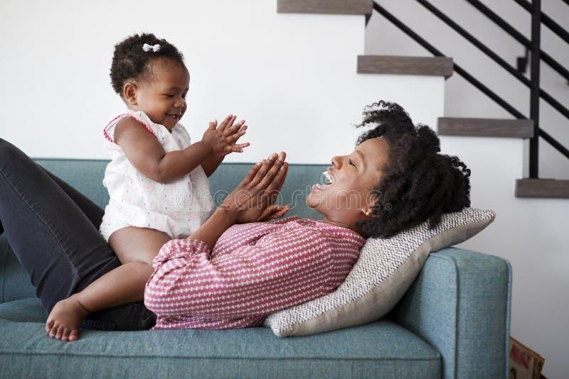 Mãe que encontra-se no jogo de Sofa At Home Playing Clapping com filha do bebê imagem de stock royalty free