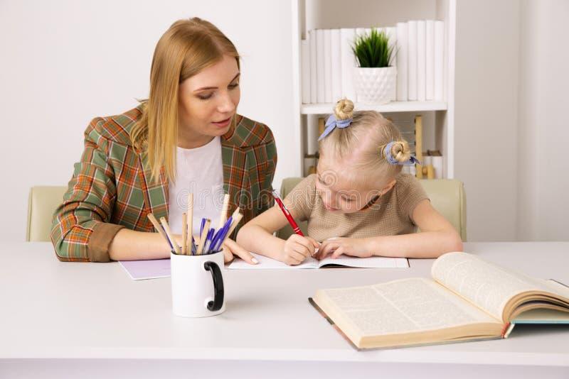 M?e que ensina a filha pequena Fazendo o conceito dos trabalhos de casa em casa imagem de stock royalty free