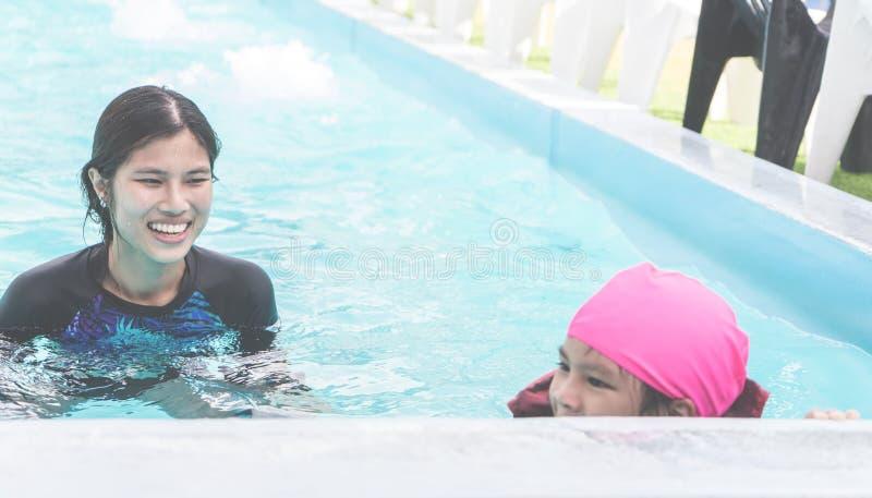 Mãe que ensina sua filha nadar imagens de stock royalty free