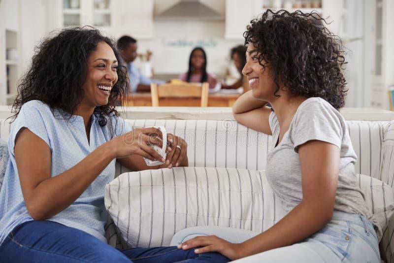 Mãe que fala com a filha adolescente no sofá imagem de stock