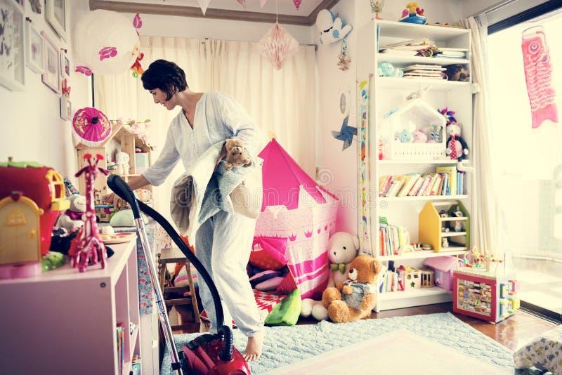 Mãe que faz a sala da filha da limpeza do vácuo imagens de stock royalty free
