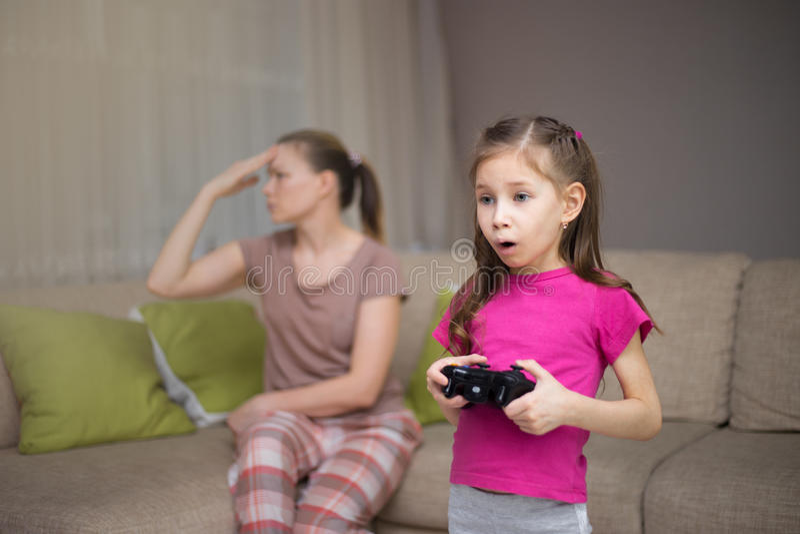 Mãe que frustra aquela seu doughter que joga jogos de vídeo foto de stock
