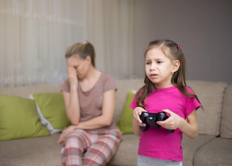 Mãe que frustra aquela sua filha que joga jogos de vídeo imagem de stock royalty free