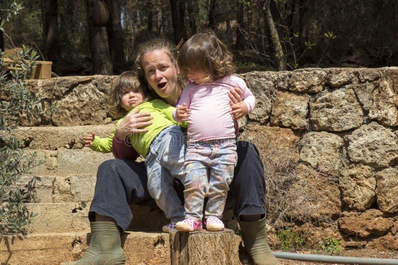 Mãe que guarda meninas gêmeas impertinentes imagens de stock