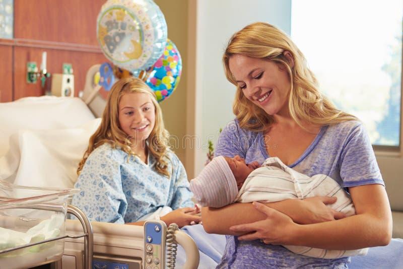Mãe que guarda o bebê recém-nascido de filha adolescente no hospital imagens de stock