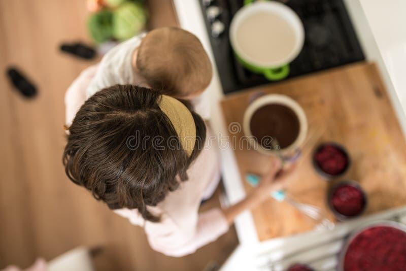 Mãe que guarda seu bebê em uma mão que faz bolos deliciosos com a outro imagens de stock