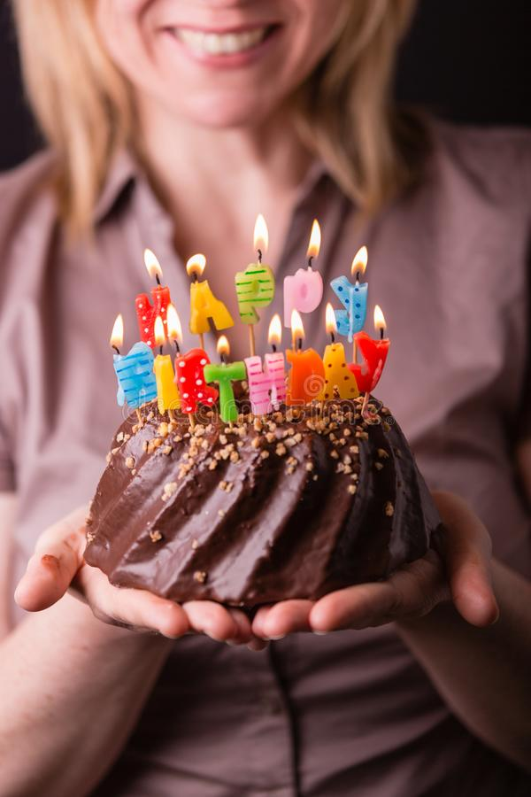 Mãe que guarda um bolo de aniversário com velas coloridas Conceito do anivers?rio, do partido e de fam?lia fotografia de stock