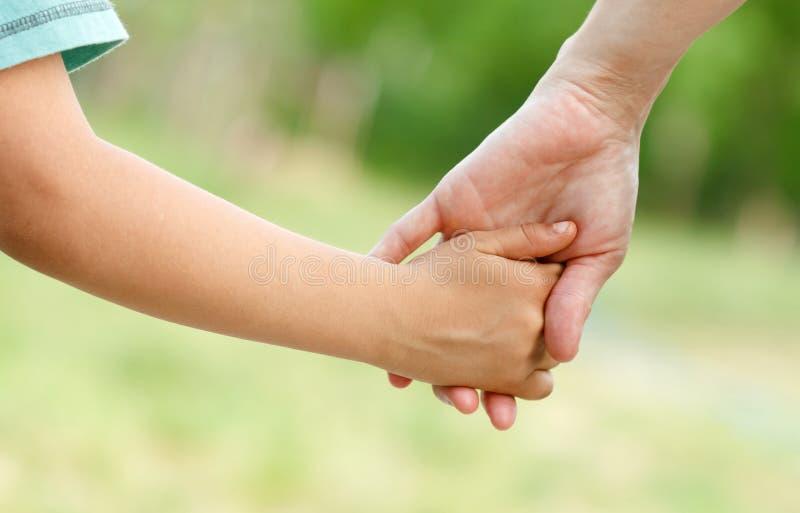 Mãe que guarda uma mão de seu filho foto de stock