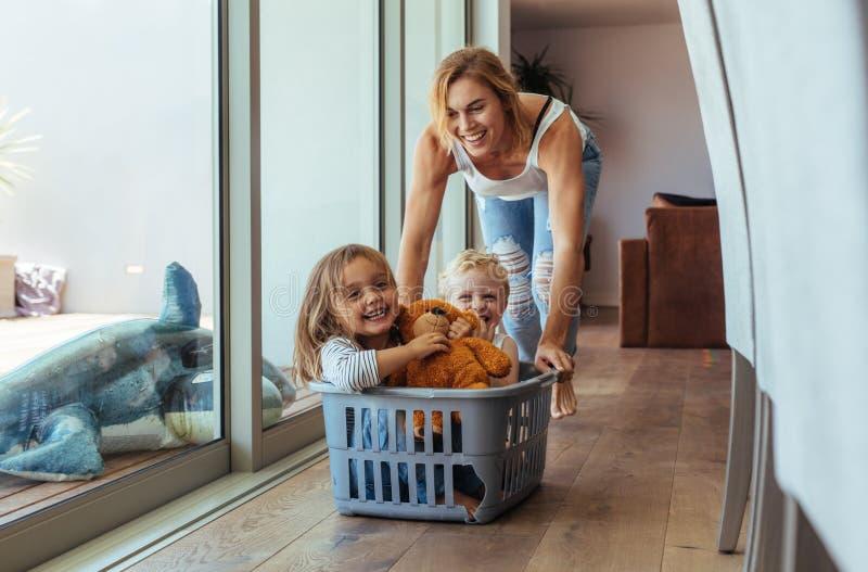 Mãe que joga com suas crianças em casa fotos de stock