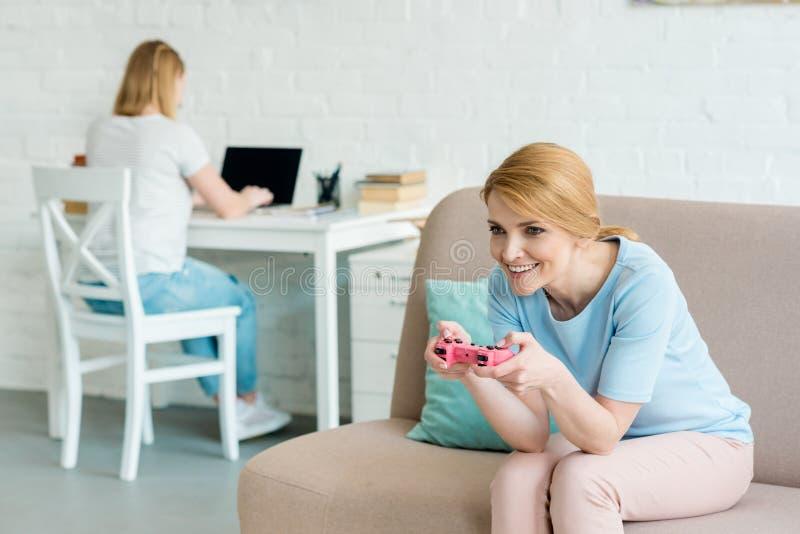 mãe que joga o jogo do console quando sua filha que trabalha com o portátil borrado imagem de stock royalty free