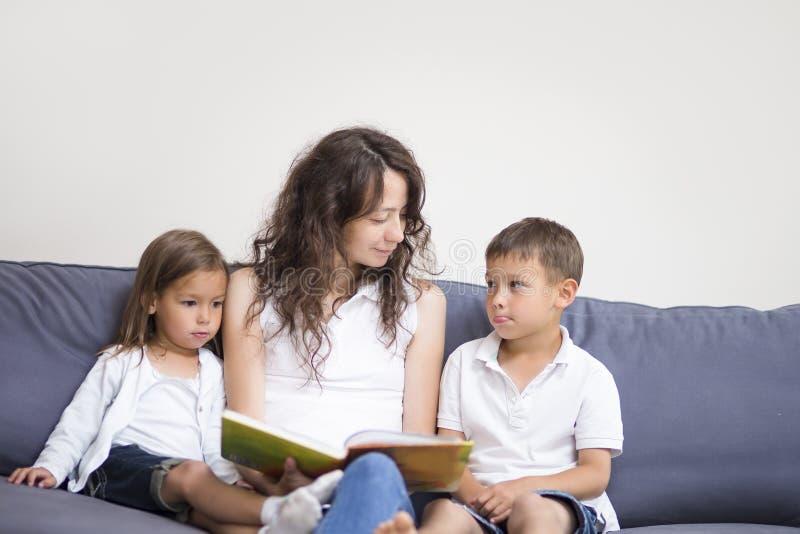 Mãe que lê um livro junto com suas crianças fotos de stock