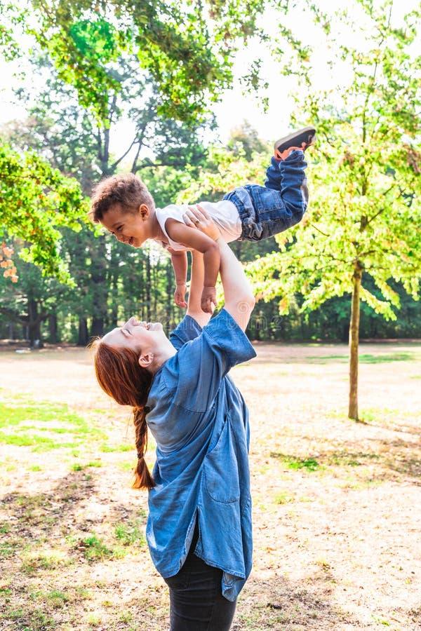 Mãe que lanç acima do filho para o divertimento no parque no dia ensolarado fotos de stock