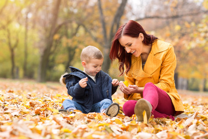 Mãe que mostra a folha amarela à criança fotos de stock royalty free