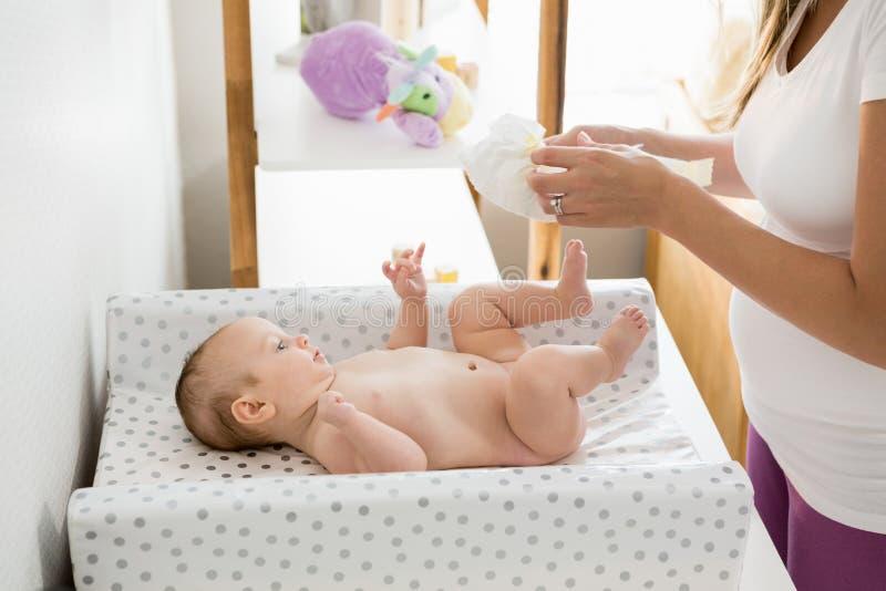 Mãe que muda o tecido de seu bebê foto de stock royalty free