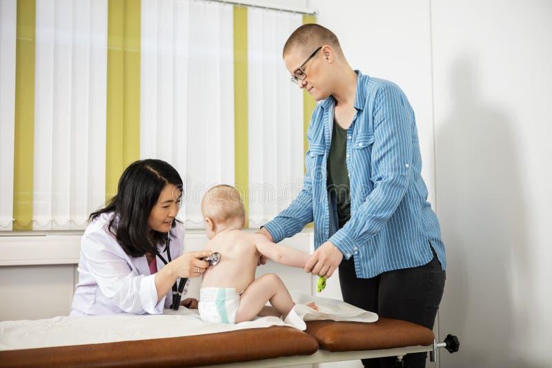 Mãe que olha a cama fêmea de Examining Baby On do pediatra imagem de stock royalty free