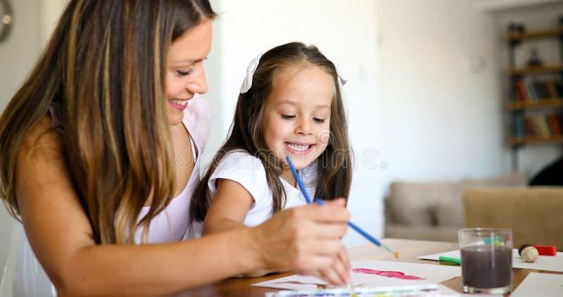 Mãe que olha como seu desenho da filha da criança fotografia de stock royalty free