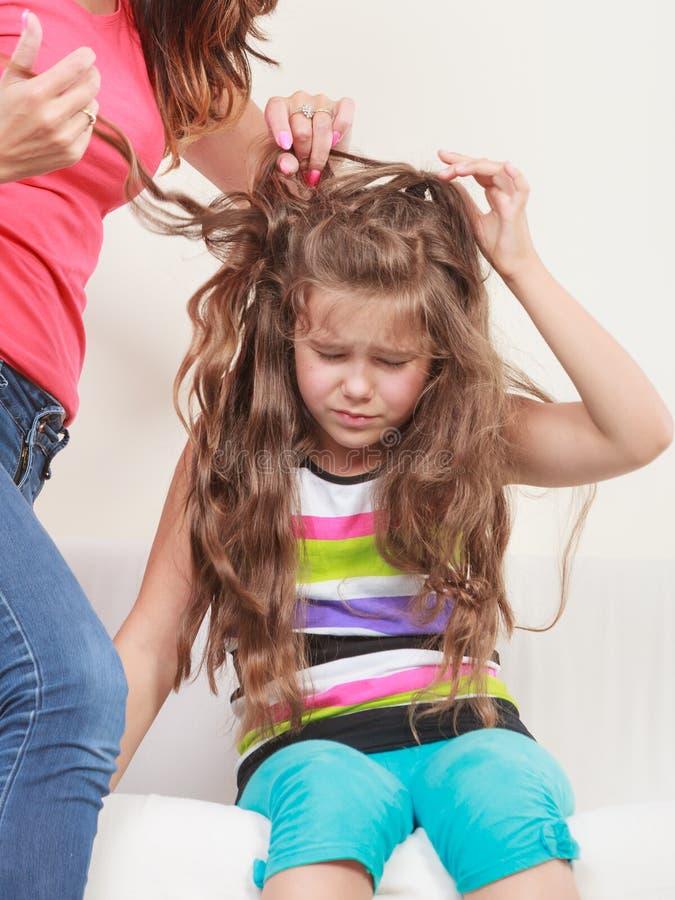 Mãe que penteia o cabelo para a filha imagens de stock