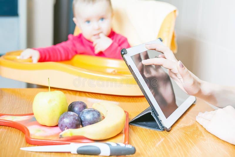 Mãe que procura a receita da preparação do comida para bebê fotografia de stock royalty free