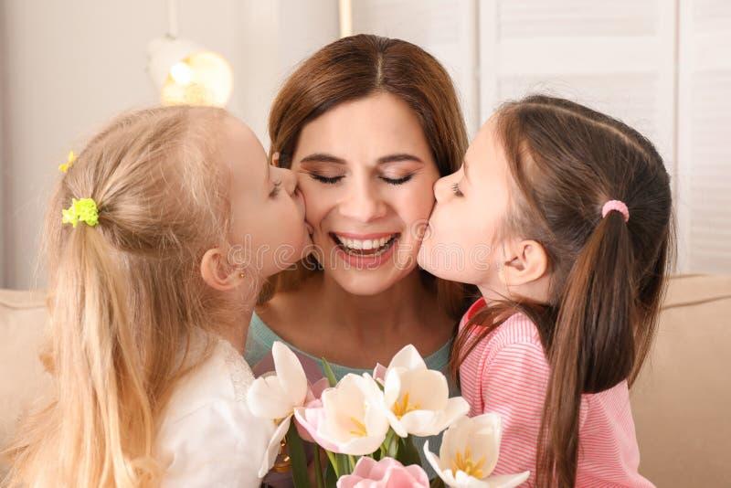 Mãe que recebe flores de suas filhas pequenas bonitos em casa fotografia de stock