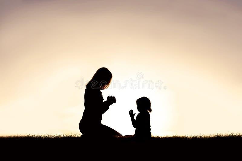 Mãe que reza com sua parte externa da jovem criança no por do sol fotos de stock royalty free