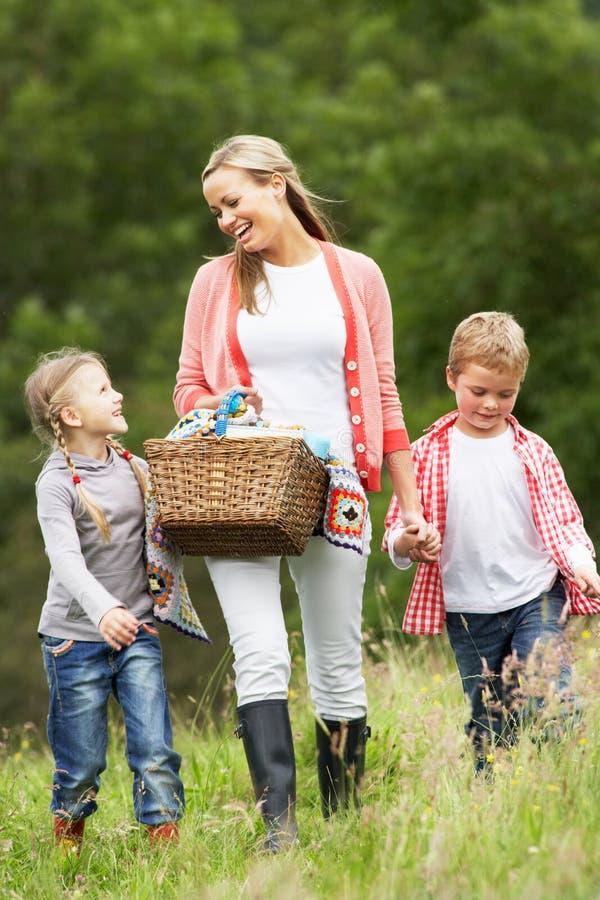 Mãe que toma crianças no piquenique no campo fotografia de stock