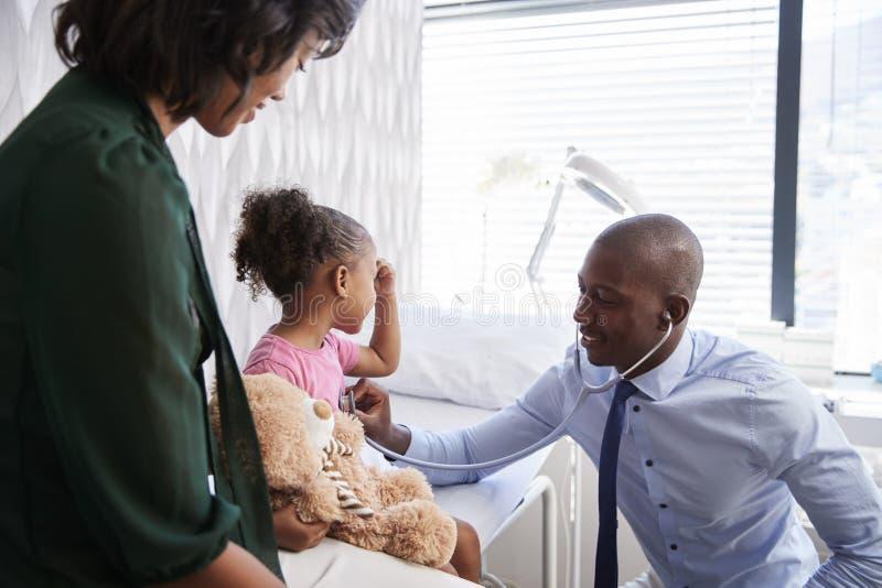 Mãe que toma a filha para o exame médico nos doutores Escritório fotografia de stock royalty free
