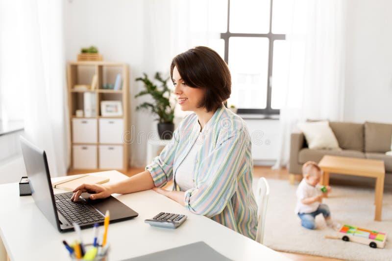 Mãe que trabalha no portátil e no bebê em casa imagem de stock royalty free