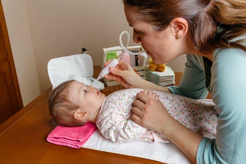 Mãe que usa o aspirador nasal com seu bebê imagem de stock royalty free