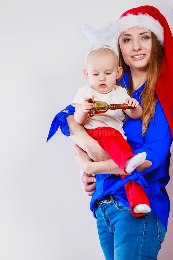 Mãe que veste o chapéu de Santa que guarda o bebê fotos de stock royalty free