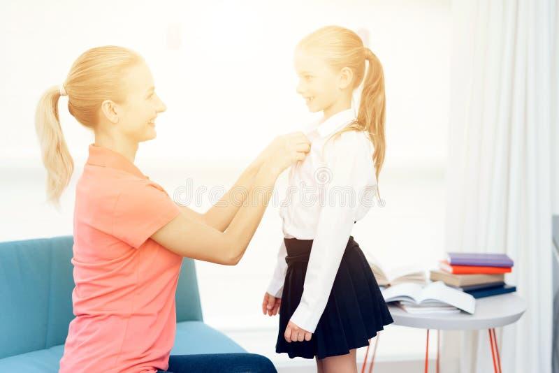 A mãe recolhe sua filha à escola As ajudas da mãe vestem uma menina imagem de stock royalty free