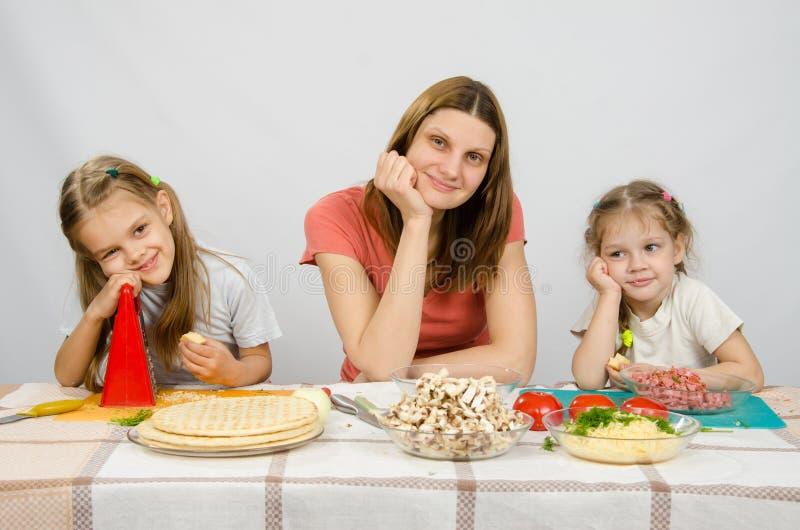 Mãe satisfeita com as duas filhas que sentam-se descansando sua cabeça em suas mãos na tabela com os produtos para a pizza fotografia de stock