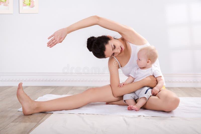 Mãe saudável e bebê que fazem a ginástica imagem de stock