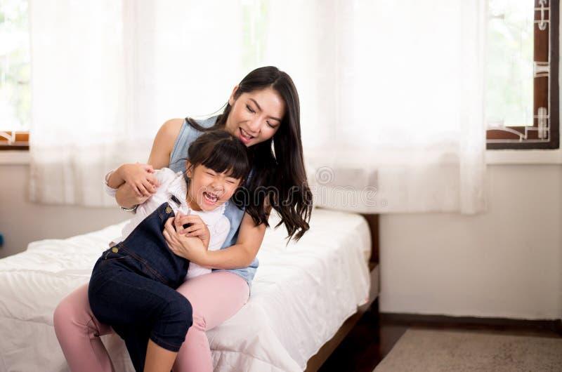 A mãe solteira asiática seja estimulada facilmente e levando sua filha alegre em casa, feliz e engraçado fotos de stock