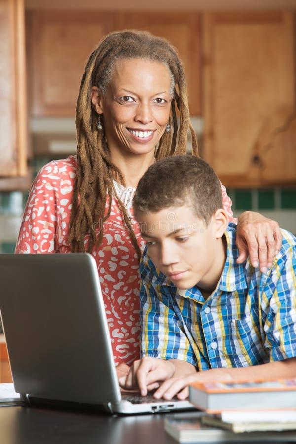 A mãe solteira e seu filho adolescente trabalham no computador fotos de stock royalty free