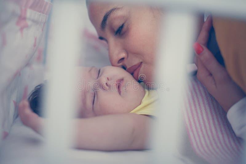 Mãe solteira que beija seu bebê pequeno no mau Fim acima foto de stock royalty free