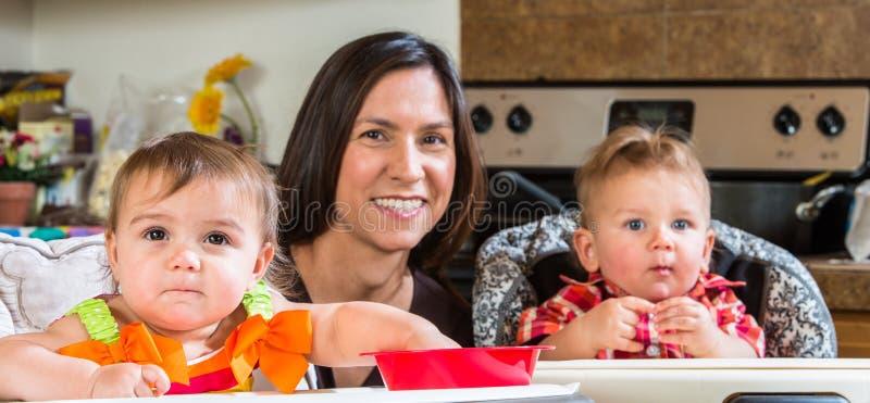 A mãe sorri com bebês foto de stock