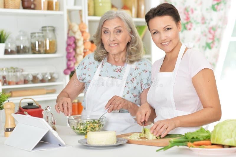 Mãe superior de sorriso e filha adulta que cozinham junto foto de stock