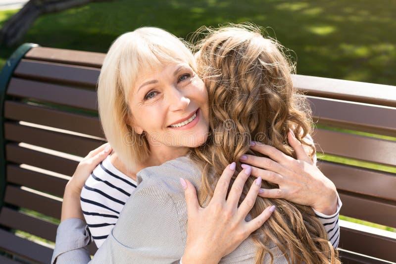 Mãe superior feliz que abraça com a filha no parque imagem de stock