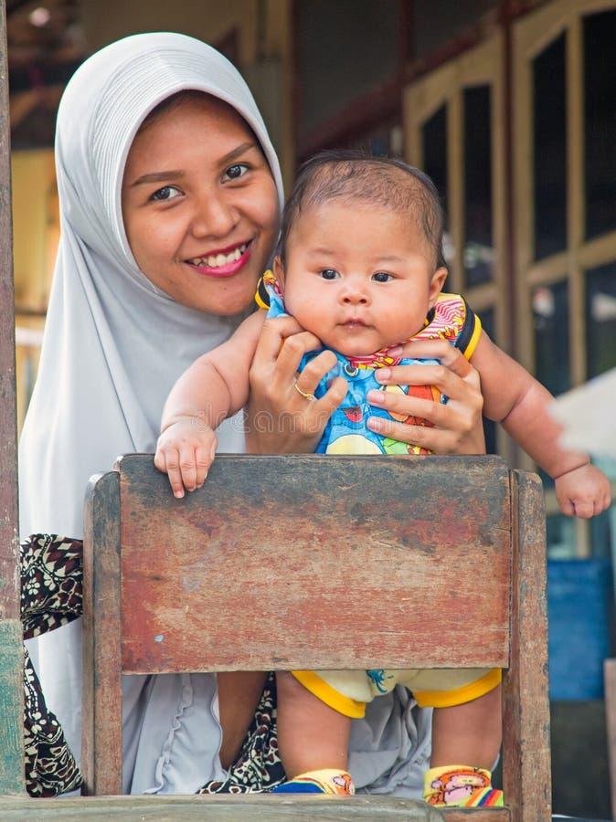Mãe tipicamente indonésia com seu bebê pequeno em Lombok, Indonésia fotos de stock