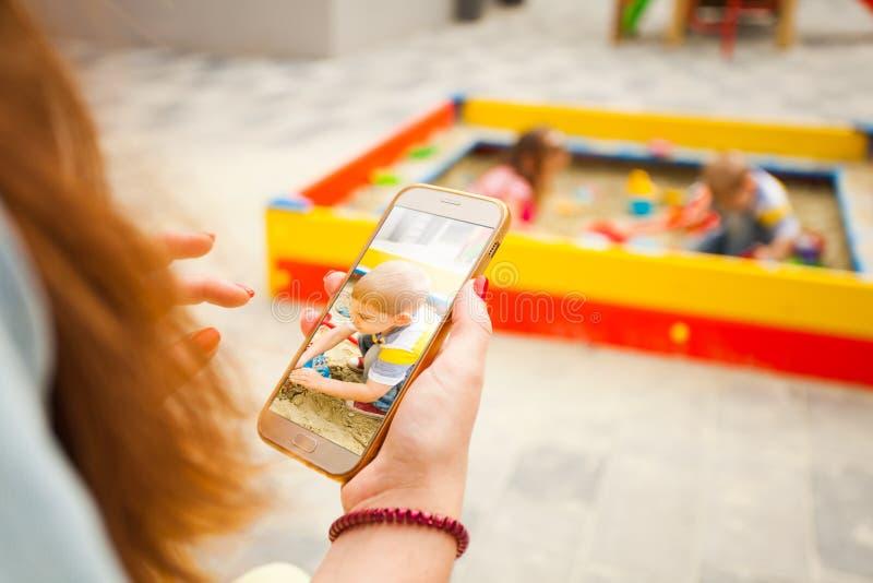 Mãe tirando foto de seu filho e postando fotografia de stock royalty free
