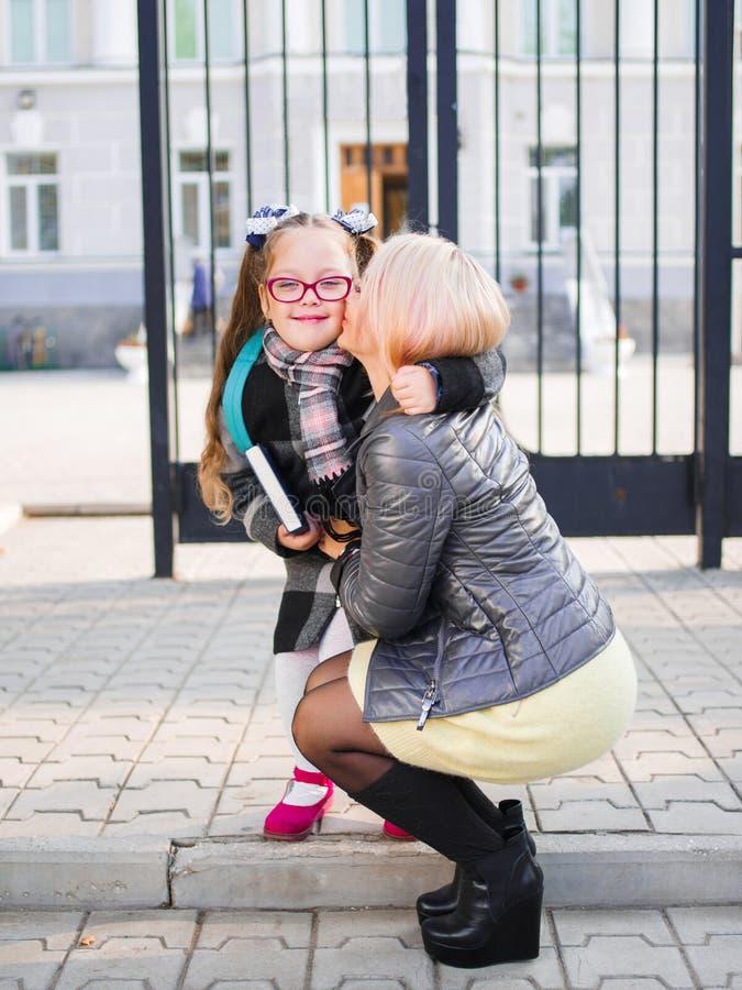A mãe toma sua filha da escola, beija a filha, conceito de família imagem de stock royalty free