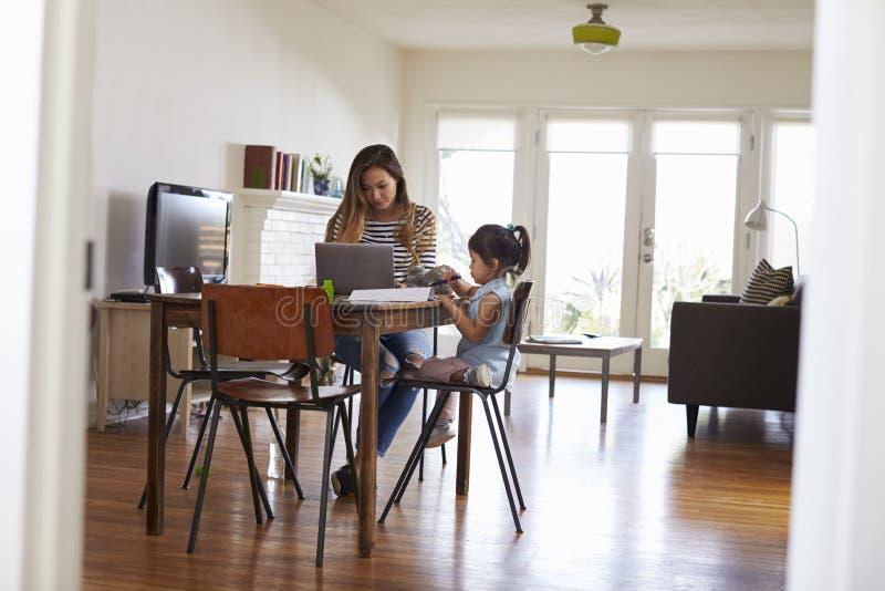 A mãe trabalha no portátil enquanto a filha tira a imagem no livro imagem de stock