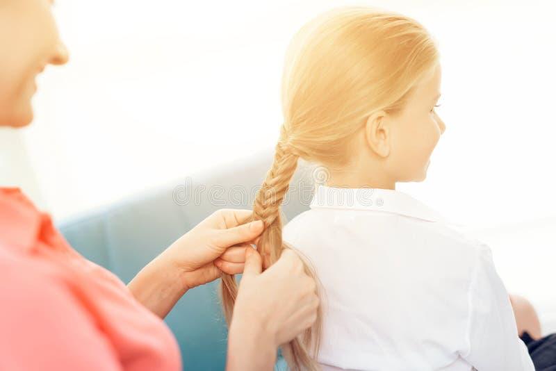 A mãe trança seu cabelo do ` s da filha Uma mulher entrança uma trança uma menina imagem de stock royalty free