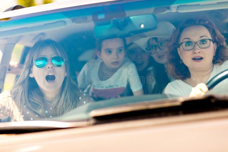 Mães com as filhas assustados em automobilístico amedrontado pelo acidente entrante foto de stock