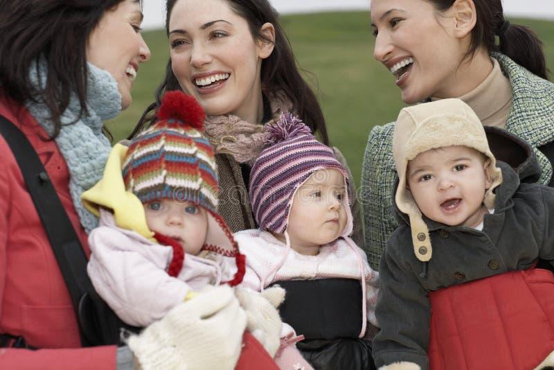 Mães com os bebês nos estilingues no parque imagem de stock royalty free