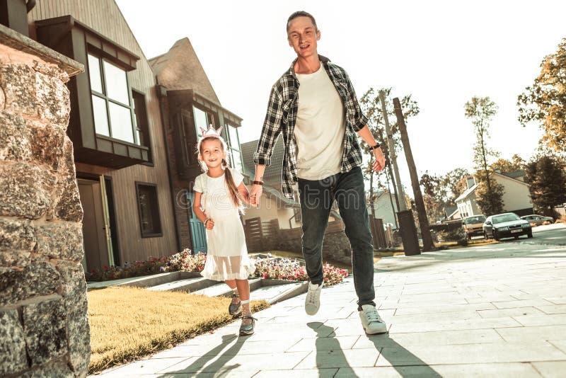 Mão à moda ativa da terra arrendada do indivíduo de sua criança ao correr foto de stock