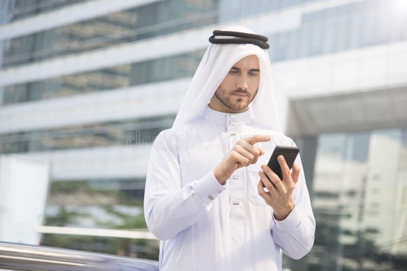 Mão árabe do homem de negócios usando o telefone celular foto de stock royalty free